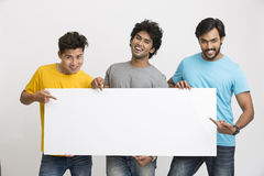 Cheerful happy friends holding white boad Stock Image