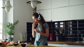 Attractive happy girl dancing and singing in kitchen while using smartphone and listening to music at home in the. Cheerful happy girl dancing and singing in stock video