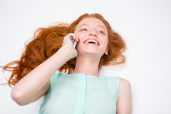 Cheerful happy girl lying and talking on mobile phone Royalty Free Stock Photography