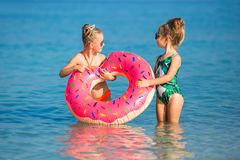 Cheerful happy girls have a rest on the sea. Two happy little girls rest on the sea. Smiling girl swimming in a circle in the sea stock photography