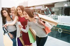 Cheerful and happy girls are standing one after another and looking down. Girl in red dress is pointing while asian girl. Is taking picture stock photos