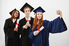 Cheerful happy graduates fooling smiling making selfie over white background. Cheerful happy graduates in caps and mantles fooling smiling making selfie over Stock Photos