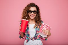 Cheerful happy lady with cola and popcorn wearing 3d glasses stock images