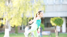 Cheerful and happy little girl dancing and playing on green grass in the park. stock video