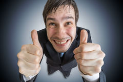 Cheerful and happy man is showing thumbs up gesture Stock Images