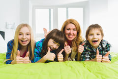 Cheerful happy mother with children lying on the bed and showing thumbs up Stock Photos