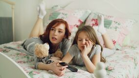 Cheerful happy mother with cute daughter watching cartoon movie on TV using remote and smiling while lying on bed at. Cheerful happy mother with little daughter stock video