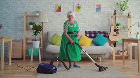 Cheerful happy old woman with gray hair vacuuming the carpet in the living room and dancing. Cheerful happy old woman with gray hair in glasses vacuuming the stock footage
