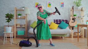 Cheerful happy old woman pensioner with gray hair in glasses playing a vacuum cleaner like a guitar. In the living room stock video footage