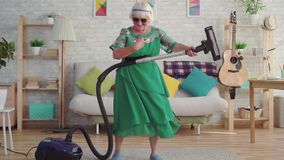 Cheerful happy old woman pensioner with gray hair in glasses playing a vacuum cleaner like a guitar slow mo. Cheerful happy old woman pensioner with gray hair in stock video footage