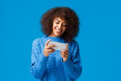 Cheerful happy, smiling young african american woman playing smartphone game, holding mobile phone horizontally as