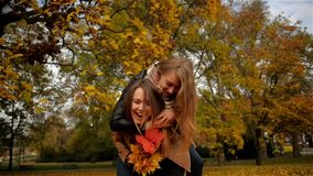 Cheerful Happy Woman Piggybacking her Pretty Girlfriend, Two Beautiful Young Girls Laughing in the Autumn Park and. Holding a Bouquet of Yellow Leaves, Funny stock video footage