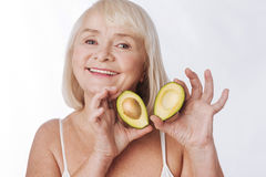 Cheerful happy woman showing you avocado halves. Useful fruit. Cheerful happy elderly woman standing against the white background and holding avocado halves Stock Photography