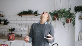 Cheerful happy woman standing on the kitchen, throw small marshmallow and catch it with her mouth. Short grey haired. Woman in modern bright kitchen standing stock footage