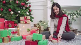 Cheerful happy young Asian woman packing and wrapping Christmas present decorate her living room at home in Christmas Festival. stock footage