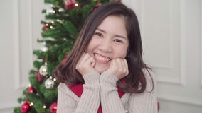 Cheerful happy young Asian woman smiling to camera in her living room at home in Christmas Festival. stock footage
