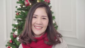 Cheerful happy young Asian woman smiling to camera in her living room at home in Christmas Festival. stock video footage