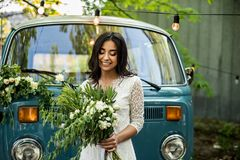 Cheerful happy young bride hold bouquet near retro-minibus. Close-up. stock photography