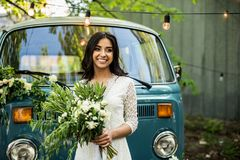 Cheerful happy young bride hold bouquet near retro-minibus. Close-up. stock image