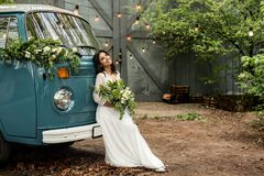 Cheerful happy young bride sit on the bumper retro-minibus. Close-up. Stock Photo