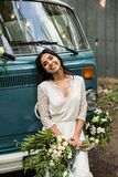 Cheerful happy young bride sit on the bumper retro-minibus. Close-up. royalty free stock images