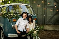 Cheerful happy young couple sit on the bumper retro-minibus. Cheerful happy young couple sit on the bumper retro-minibus royalty free stock photos