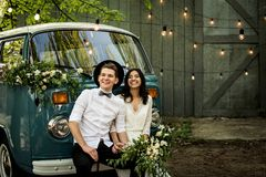 Cheerful happy young couple sit on the bumper retro-minibus. royalty free stock images