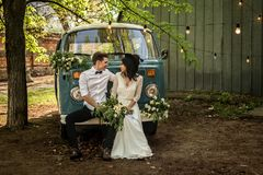 Cheerful happy young couple sit on the bumper retro-minibus. stock photo