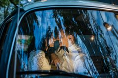 Cheerful happy young couple sit in the retro-minibus. stock photos