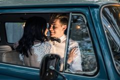 Cheerful happy young couple sit in the retro-minibus. stock images