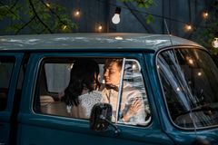 Cheerful happy young couple sit in the retro-minibus. royalty free stock photo