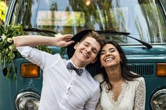 Cheerful happy young couple smiling near retro-minibus. Close-up. royalty free stock image