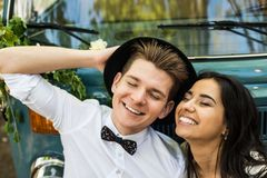 Cheerful happy young couple smiling near retro-minibus. Close-up. stock photos