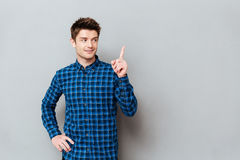 Cheerful happy young man standing over grey wall and pointing. Picture of cheerful happy young man standing over grey wall and pointing. Looking aside Stock Image