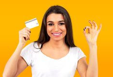 Cheerful happy young woman with credit card showing Ok sign. Beautiful cheerful happy young woman with credit card showing Ok sign on yellow background stock image