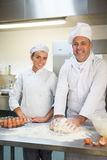 Cheerful head chef showing trainee how to prepare dough Royalty Free Stock Photography