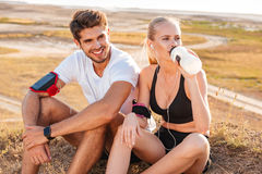 Cheerful healthy couple resting together with bottle of water. Outdoors stock photography