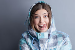 Cheerful healthy girl is drawing faces during rain. Pretty young woman is making fun in rainy weather. She is standing in raincoat and looking at camera with joy Stock Photos