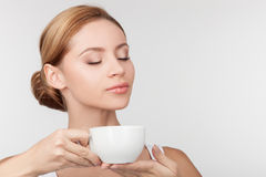 Cheerful healthy girl drinks tea with pleasure Royalty Free Stock Images