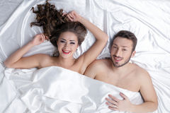 Cheerful heterosexual couple posing in bed Stock Image