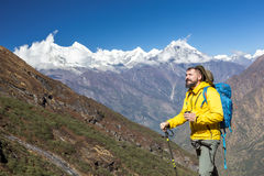 Cheerful Hiker in yellow Jacket drinking Tea in Mountains Royalty Free Stock Images