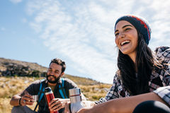 Cheerful hikers having rest on field Stock Photo