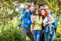 Cheerful hiking group shows with finger destination Royalty Free Stock Photos