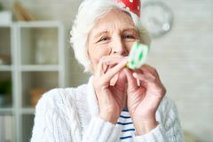 Carefree granny blowing party horn. Cheerful hilarious elderly woman with wrinkles having fun alone and blowing party horn while celebrating party at home stock photography