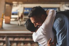 Cheerful hindu father embracing his little son. Positive smiling hindu men standing at the railway platform while embracing his little son royalty free stock image