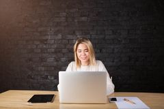 Young charming woman freelancer working in internet on laptop computer, sitting in modern interior. Cheerful hipster girl distance worker using portable net Stock Image