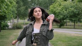 Cheerful hipster girl in good mood with long hair walks down the street and dances listening to music using a portable. Cheerful hipster girl in good mood in stock footage