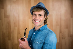 Cheerful hipster holding pipe Royalty Free Stock Image