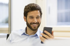 Cheerful Hipster man in office. Typing text message on mobile ph. Happy businessman using his smartphone at work Royalty Free Stock Photo