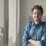 Cheerful hipster posing. Cheerful young hipster guy posing and smiling at camera with crossed arms Royalty Free Stock Photography